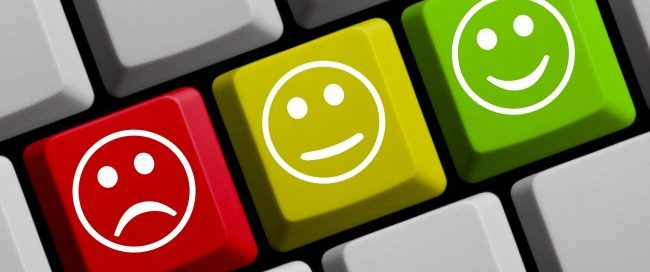 Testimonials concept, sad, content and happy faces on a keyboard