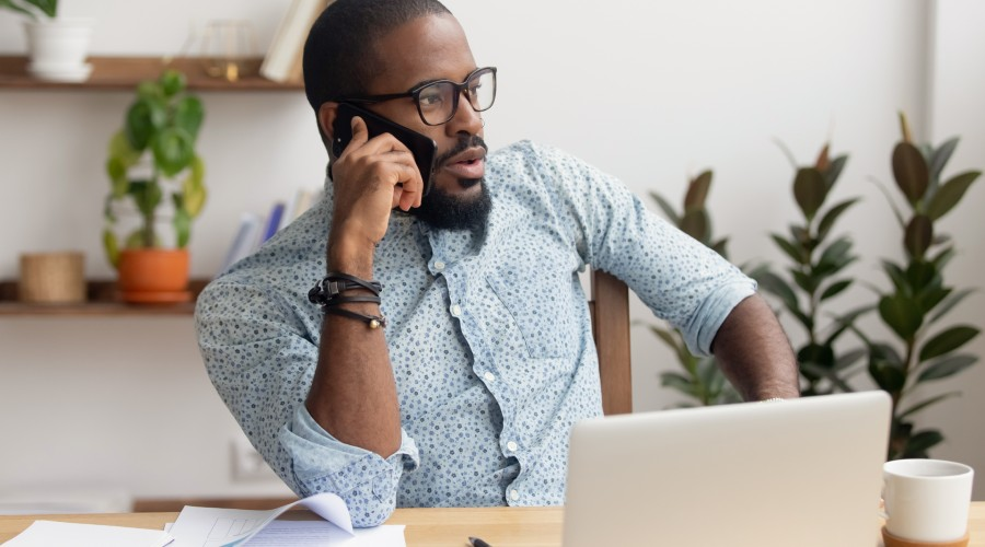 man on phone at desk infront of laptop